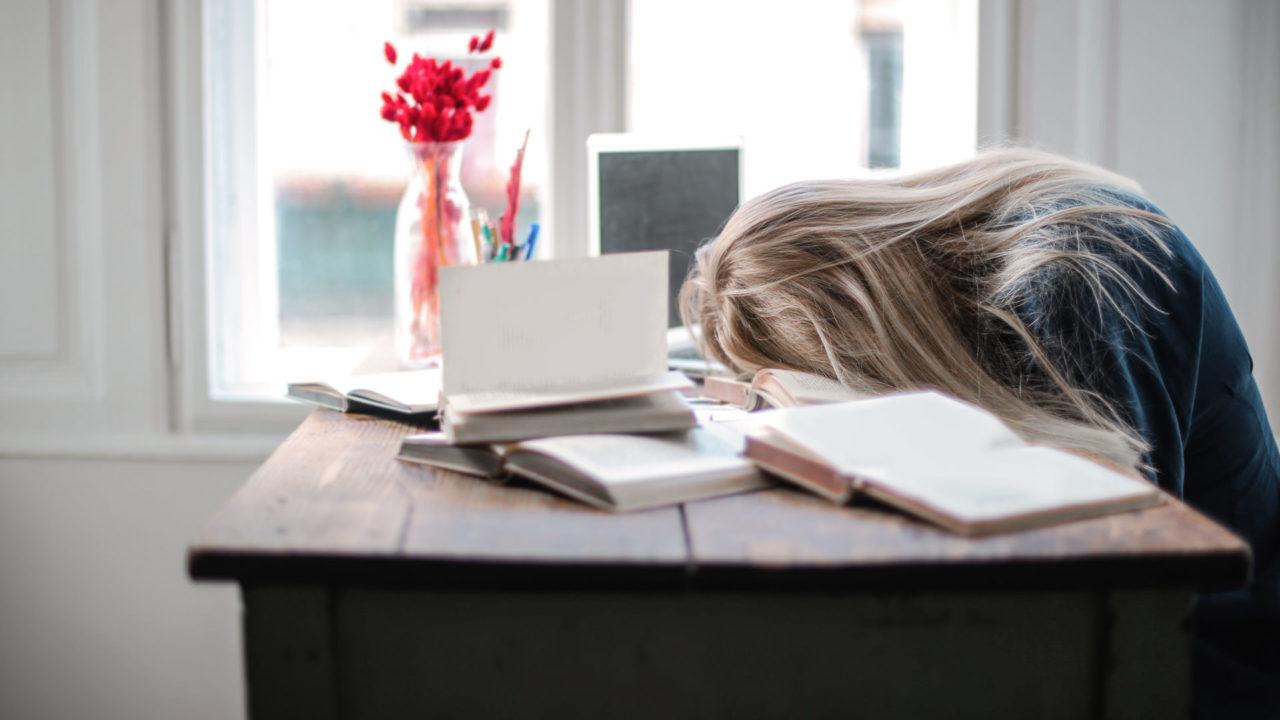 仕事机に突っ伏する女性
