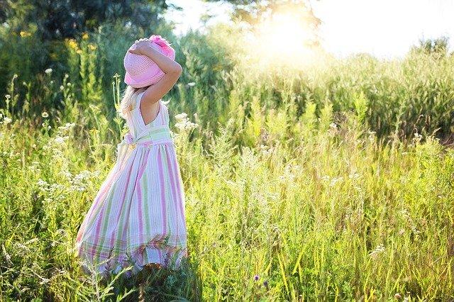 草むらで帽子を抑える少女