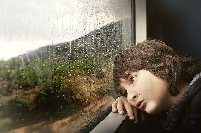 窓を眺める少年