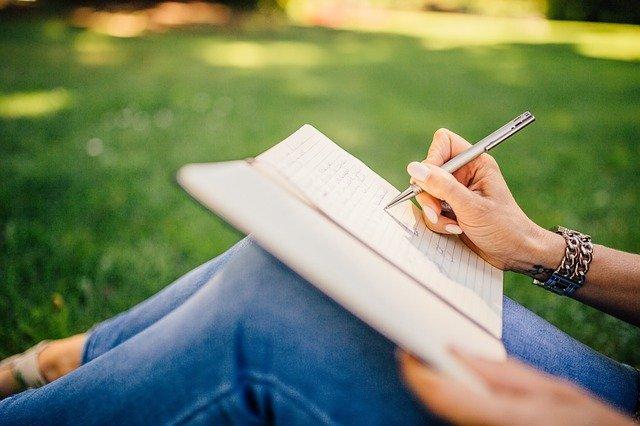 公園で筆を取る女性