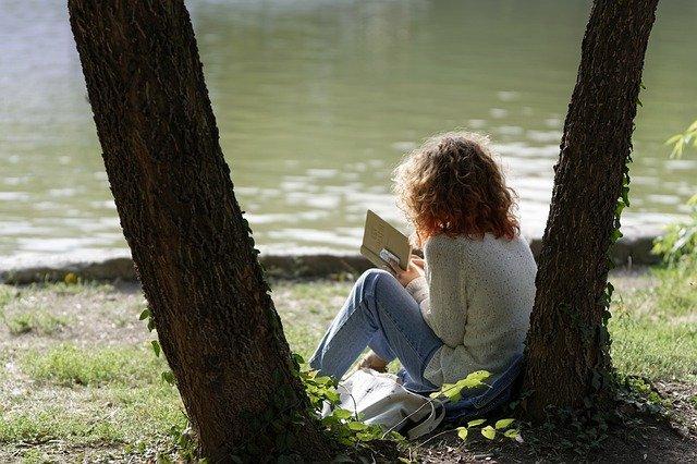湖畔で本を読む女性