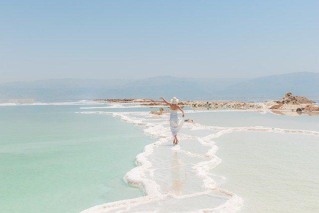海で楽しげに手をあげる女性